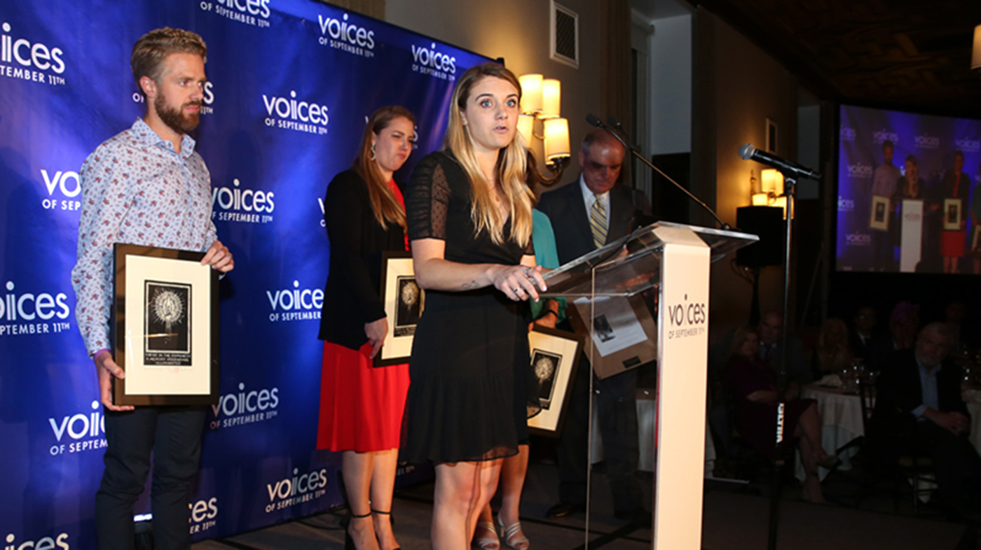 Heidi Wolfgruber '11 stands at a clear podium for a VOICES event