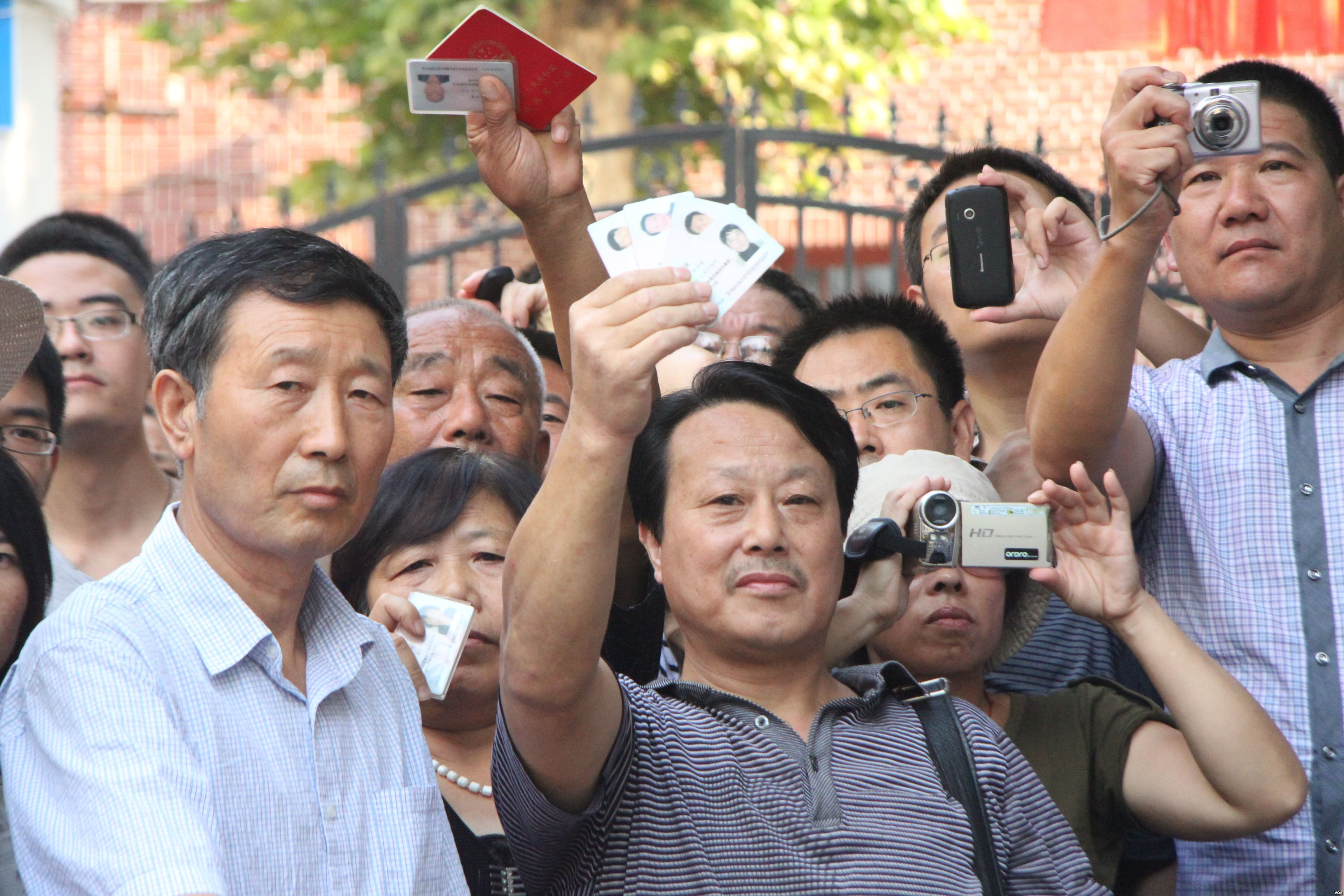Chinese citizens holding up IDs and cameras at Bo Xilai trial