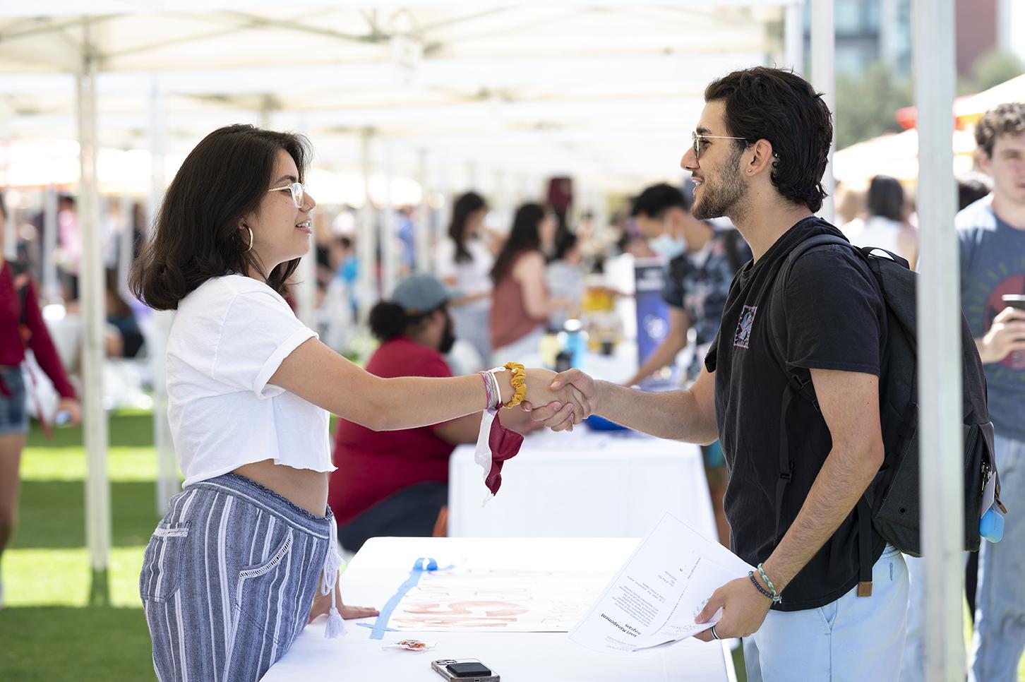 Katherine Esther Almendarez Zuniga '22 (left), Associated Students of Claremont McKenna College president, greets Mohamed Yassin '23 at her organization's booth.
