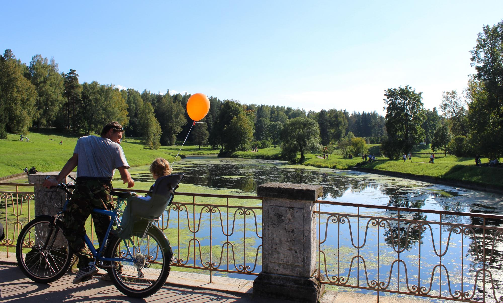 Man on bicycle with a child holding a balloon