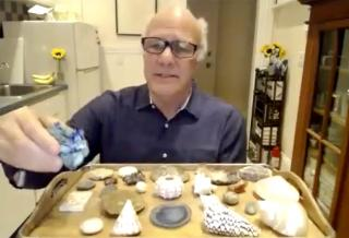 Henri Cole showing seashells during his Athenaeum talk