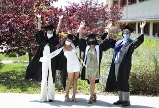 Cheering CMC grads on campus wearing caps and gowns and masks