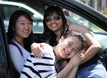 Three Female Students Sitting In Car
