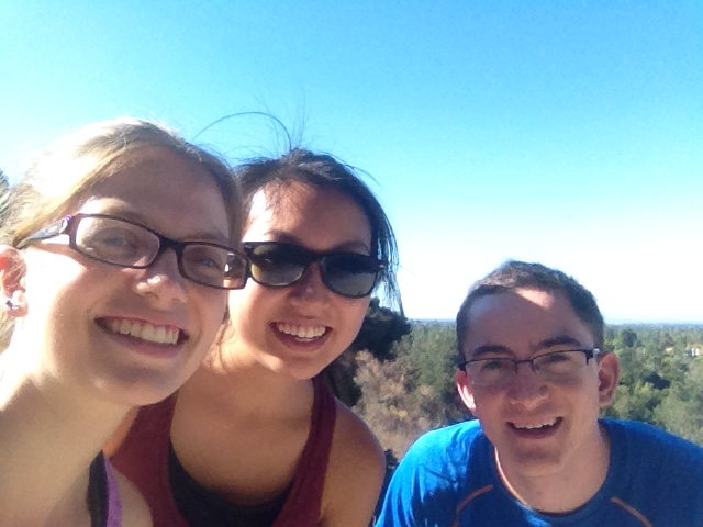 Three SVP students smiling at the top of a hill with a blue sky in the background.